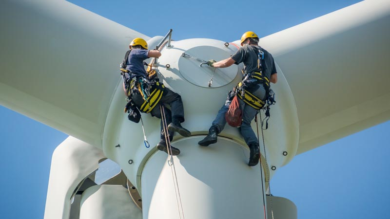 Workmen on ropes conducting repairs on a wind farm rotor